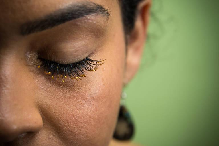 Mulher com olhos fechados e cílios cujas pontas são douradas