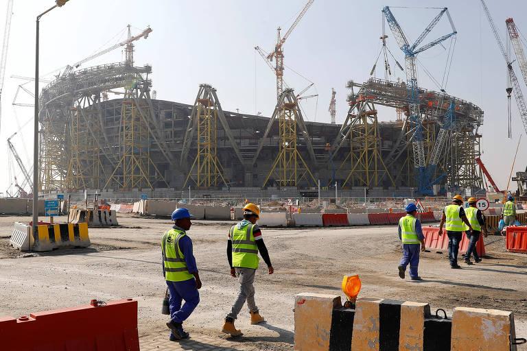Operários passam em frente ao canteiro de obras do estádio em Lusail