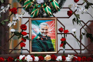 Flowers lie around portrait of Iranian Major-General Soleimani, who was killed in airstrike near Baghdad, on Iranian embassy's fence in Minsk