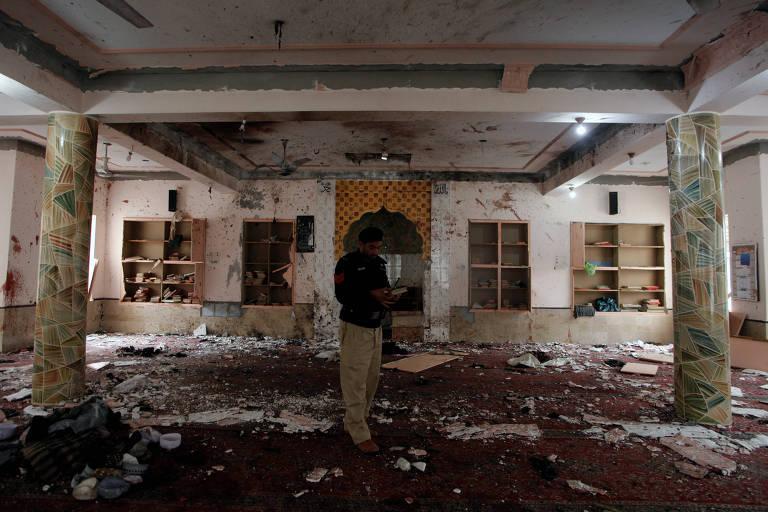 policial uniformizado está no meio de uma mesquita. Há escombros após uma explosão. É possível ver janelas com vidros quebrados, manchas que aparentam ser de sangue, fuligem e duas pilastras, uma a cada lado da imagem.
