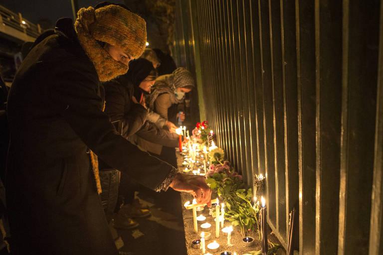 Mulheres utilizando turbantes e cobrindo os rostos acendem velas em cerimônia fúnebre. Há flores e fotos de pessoas mortas no acidente