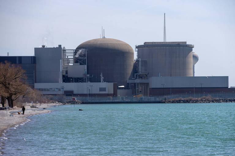 imagem mostra usina nuclear ao fundo, com construções em concreto de formatos cilíndricos e retangulares. em primeiro plano há um lago de águas verdes. Há um homem na margem do lago, mas não é possível distinguir se é um funcionário