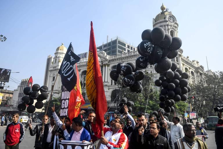 grupo pessoas, cerca de 30, segura bandeiras vermelhas e balões pretos sim sinal de protesto