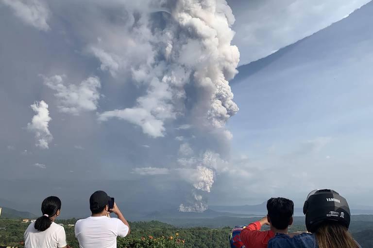 Turistas fotografam nuvem de fumaça expelida pelo vulcão Taal