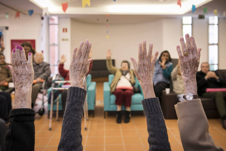 idosos sentados em cadeiras fazem exercícios com os braços