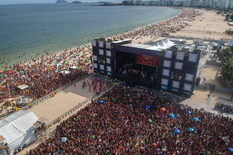 Palco na praia repleta de gente sob o sol