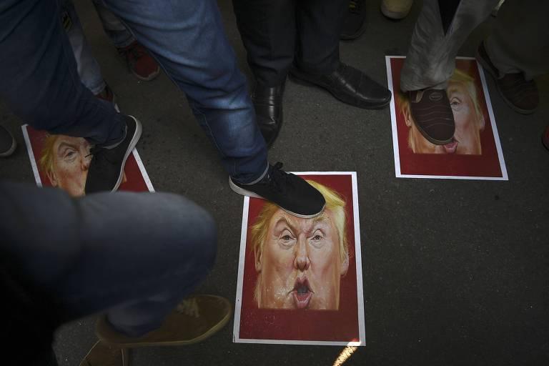 Manifestantes pisam em cartazes com rosto de Trump em ato contra a morte do general Qassim Suleimani em Nova Déli