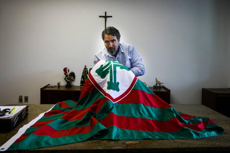 O novo presidente da Portuguesa, Antonio Carlos Castanheira, segura a bandeira do clube em sua sala
