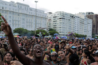 People dance during the opening show of the pre-carnival at the Copacabana beach in Rio de Janeiro