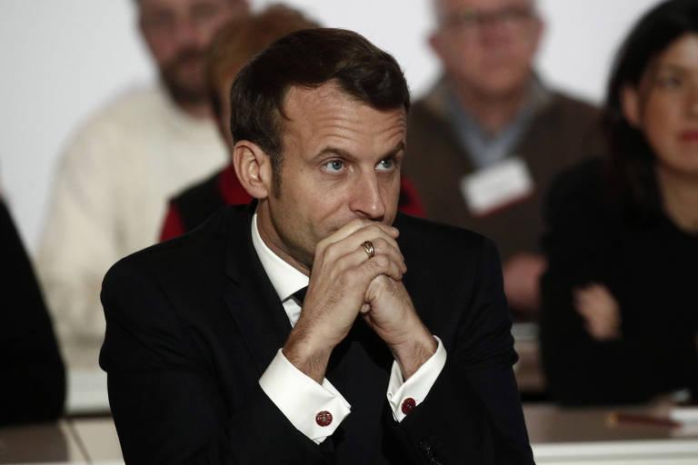 Macron apoia o queixo nas mãos e olha para o lado