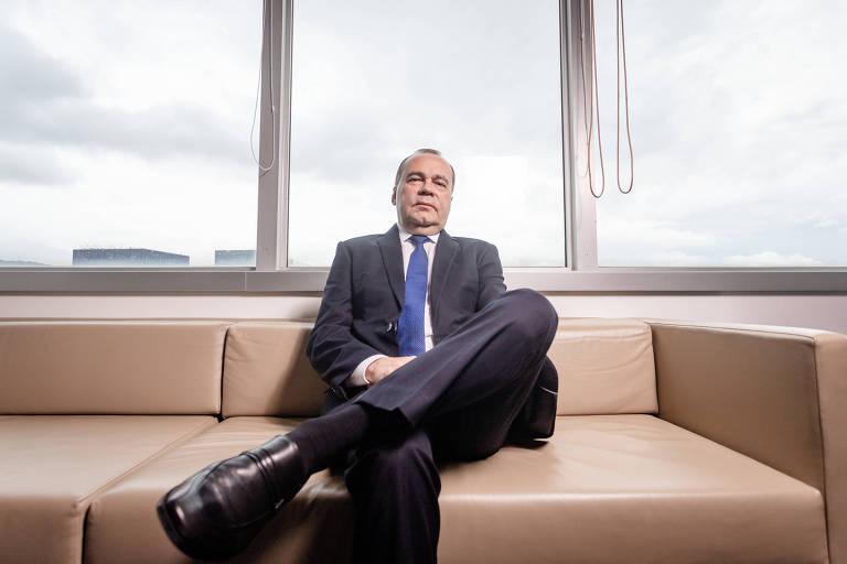 Na foto, o presidente da Líder Seguradora aparece sentado com as pernas cruzadas sobre um sofá bege. O semblante é sério e as mãos se encontram cruzadas no colo