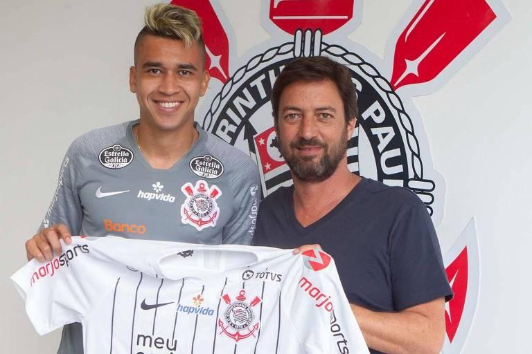 O diretor de futebol do Corinthians, Duílio Monteiro Alves, acompanhado do  volante Victor Cantillo, segura a camisa do clube