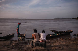 People wait for fishermen to arrive with fish, in Parmana, a fishing village on the banks of the Orinoco River in central Venezuela, on Dec. 4, 2019. (Adriana Loureiro Fernandez/The New York Times)