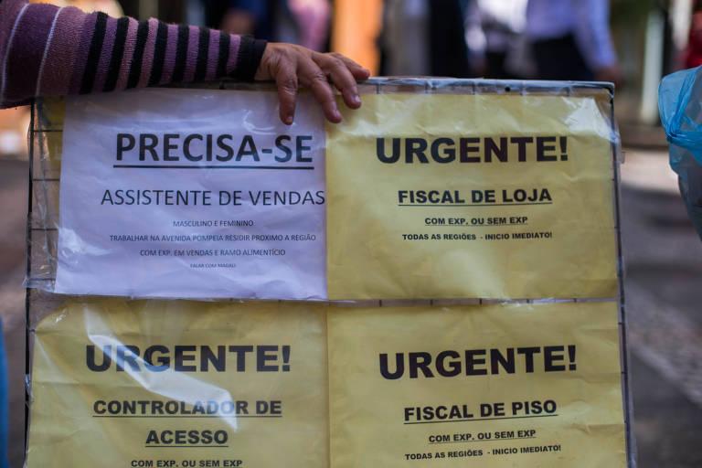 Foto com uma placa com anúncios de emprego como fiscal de loja e assistente de vendas