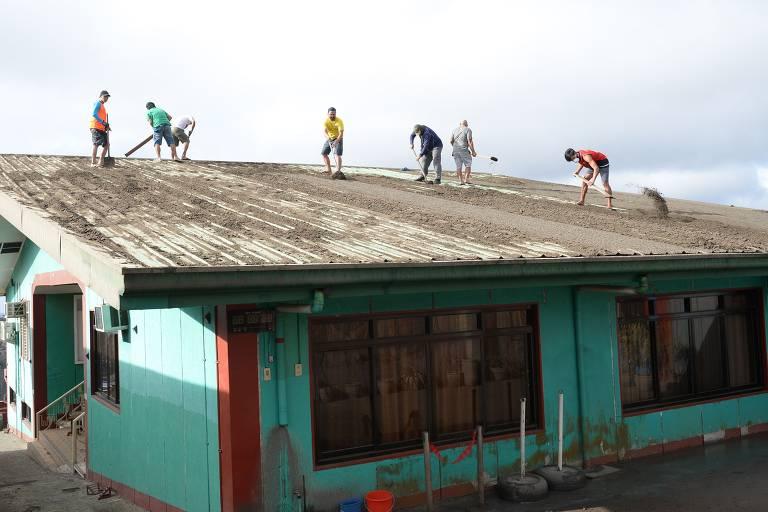 Sete homens estão no telhado de um imóvel de cor verde, limpando a cinza acumulada