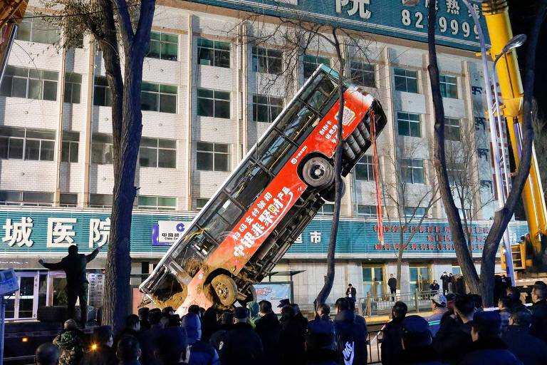 Ônibus é erguido após cair em vala que se abriu em asfalto em Xining, na China