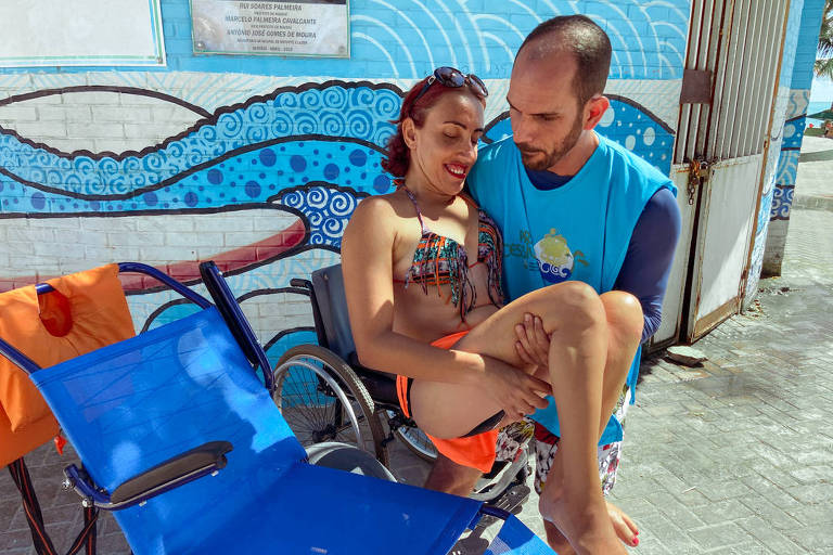 Homem com colete azul carrega mulher em trajes de banho em direção a cadeira de rodas adaptada para água (com tecido diferente e rodas maiores)