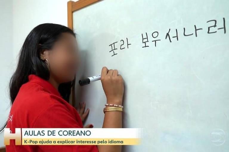 Uma menina de roupa vermelha escreve em coreano em uma lousa branca