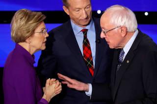 Democratic 2020 U.S. presidential candidates Senator Elizabeth Warren (D-MA) speaks with Senator Bernie Sanders as billionaire activist Tom Steyer listens after the seventh Democratic 2020 presidential debate at Drake University in Des Moines