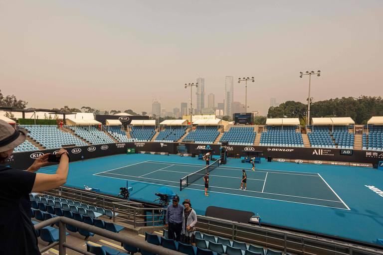 Com o céu cinza pela fumaça, turista tira foto de uma das quadras onde é disputado o Aberto da Austrália