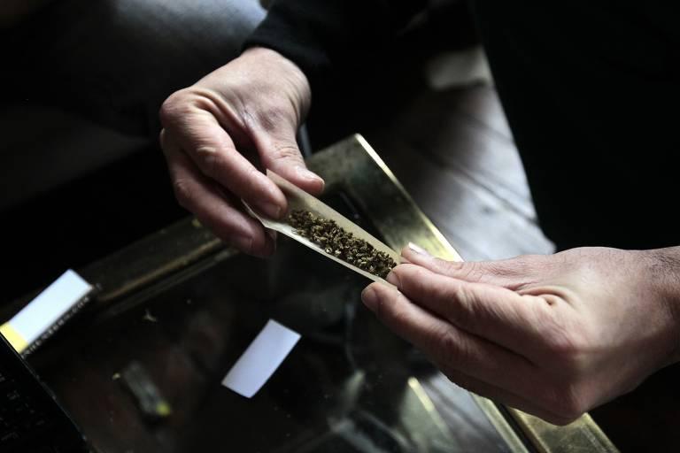 Pessoa manipula cigarro de maconha