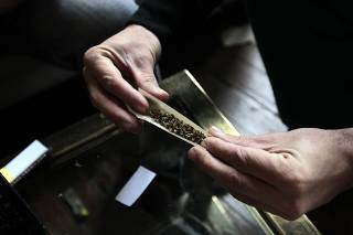 A judge rolls a marijuana cigarette during a judging session at Uruguay's second