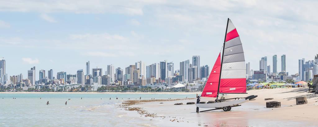 Barco a vela pequeno na areia, em praia com cidade ao fundo