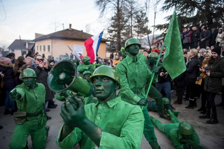 Foliões fantasiados de soldados desfilam pelas ruas de Vevcani, na Macedônia do Norte, durante o Carnaval