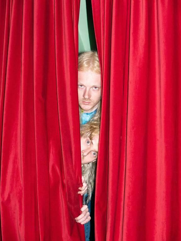 duas pessoas loiras no meio de uma cortina vermelha