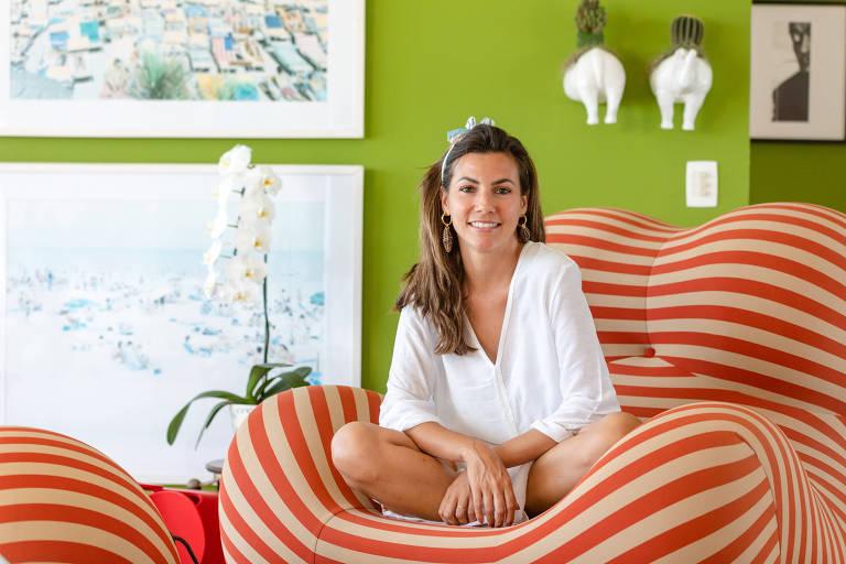 Na foto, a florista Nicole Tamborindeguy aparece sentada em um sofá laranja de listras brancas. As pernas dela estão cruzadas em cima do sofá e as mãos descansam cruzadas, com os cotovelos apoiados no joelho. Ela veste um vestido branco liso de mangas três quartos e olha sorridente para a câmera