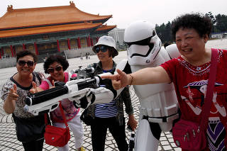 Tourists from China pose with a man dressed as a Storm Trooper from