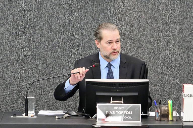 Dias Toffoli sentado à uma mesa, com tela de computador à sua frente, fala ao microfone. Ao fundo parece cinza escuro.