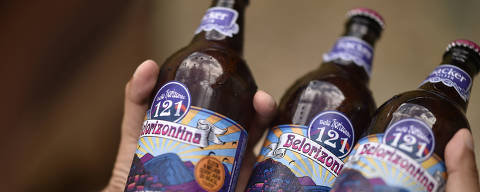 A man holds bottles of 'Belorizontina' beer in Belo Horizonte, on January 15, 2020. - Brazilian authorities are investigating the deaths of at least two people who drank contaminated beer with diethylene glycol -a widely used solvent- in the state of Minas Gerais (southeast), police and the federal government said. The substance was found in samples of Belorizontina beer, manufactured by the local company Backer, collected in the victims' house and also inside the factory, the Minas Gerais Civil Police reported. (Photo by DOUGLAS MAGNO / AFP)