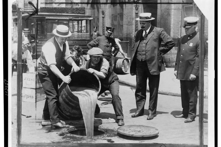 Vice-comissário de polícia de Nova York (à dir.) assiste a agentes derramarem bebida alcoólica no esgoto após uma fiscalização no auge da Lei Seca