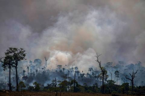 (FILES) In this file photo taken on August 27, 2019 smokes rises from forest fires in Altamira, Para state, Brazil, in the Amazon basin. - Four people accused of starting fires in the Amazon rainforest to later receive international funds to combat them, were arrested in Brazil on November 26, 2019. Environmentalists denounced an alleged campaign of Brazilian President Jair Bolsonaro to discredit their work and condemned the measure as
