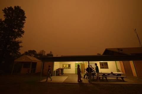 TOPSHOT - People gather in the community hall as the sky turns orange from bushfires in Towamba, 20km from Eden, in southern New South Wales on January 10, 2020. - The fires have claimed at least 26 lives and destroyed more than 2,000 homes across Australia. (Photo by PETER PARKS / AFP) ORG XMIT: PP9834