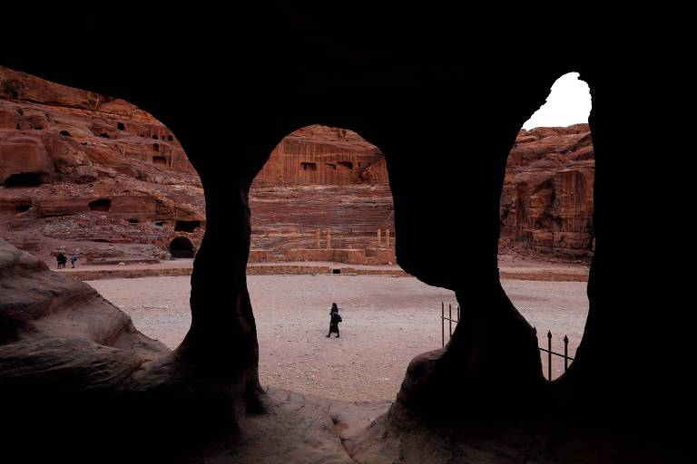 Pessoa caminha por espaço cercado de paredes de pedra avermelhada