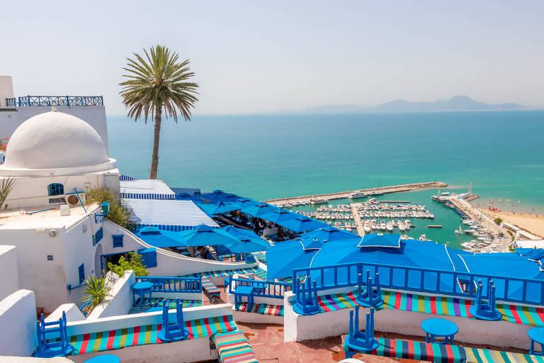 Varanda com bancos azuis e vista para mar de cor clara