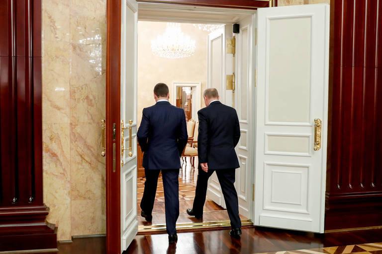 Putin (dir.) e Dmitri Medvedev, deixam reunião após o anúncio da demissão do então premiê