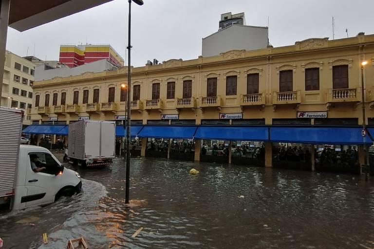 Caminhão tenta passar por rua alagada; ao fundo, loja com comportas para evitar enchente