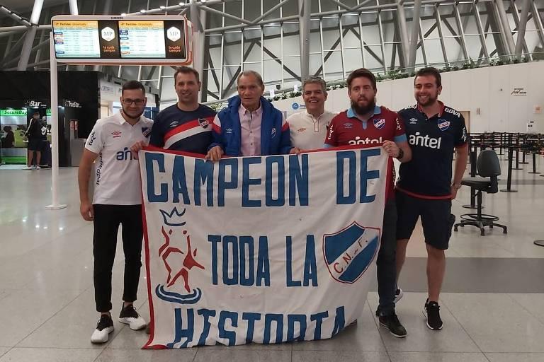 Manga, de casaco azul ao centro, se despede dos torcedores do Nacional no aeroporto de Carrasco, no Uruguai