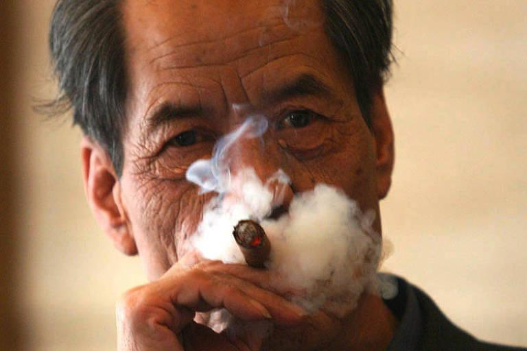 homem oriental fumando charuto