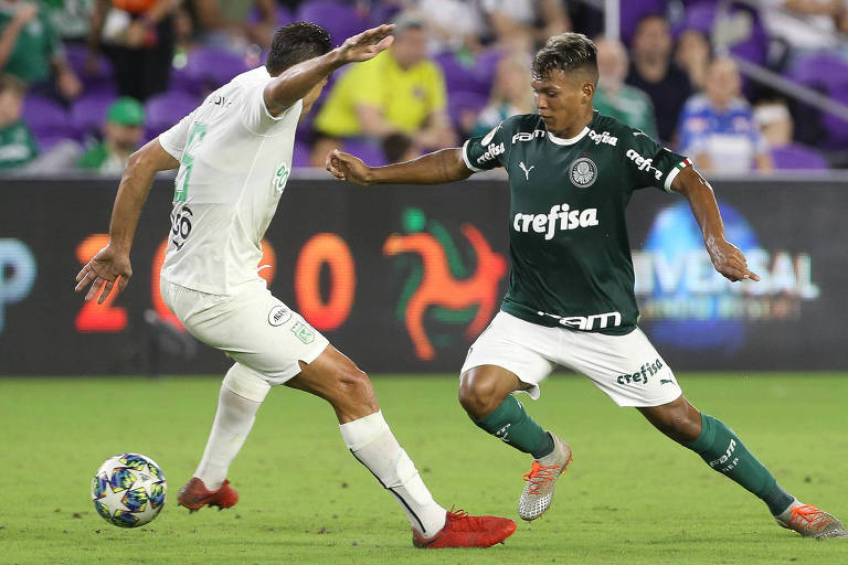 O garoto palmeirense Gabriel Veron escapa da marcação do zagueiro  Diego Braghieri, do Atlético Nacional