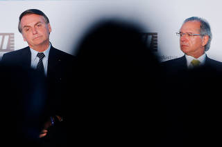Brazil's President Jair Bolsonaro looks on near Brazil's Economy Minister Paulo Guedes during a meeting with businessmen at the National Confederation of Industry (CNI) in Brasilia