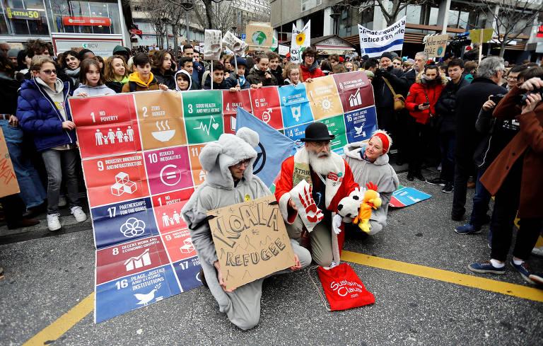 Manifestantes, um deles vestido como coala, são rodeados por observadores na rua