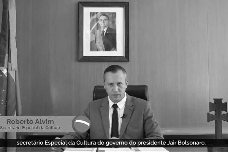 Imagem mostra Roberto Alvim ao centro, sentado em uma mesa; acima dele, a foto do presidente Jair Bolsonaro; ao seus lados, a bandeira brasileira e uma cruz
