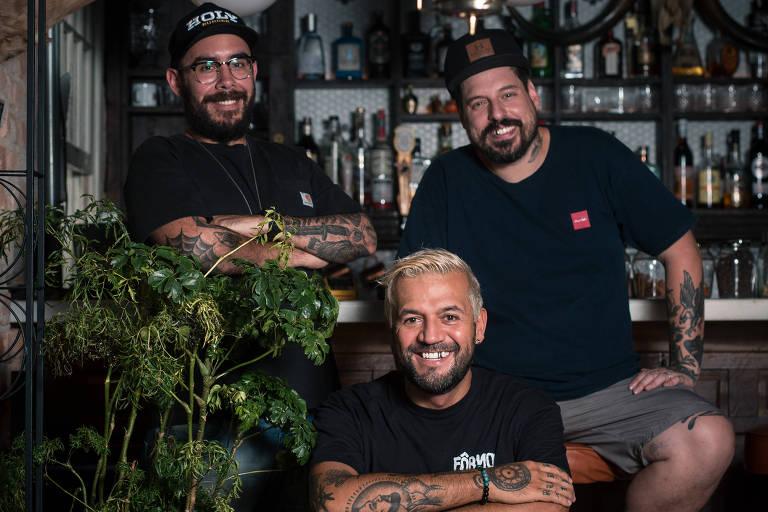 Três homens de camisetas pretas aparecem sorrindo para retrato em grupo. Ao fundo, está um balcão e estante com bebidas