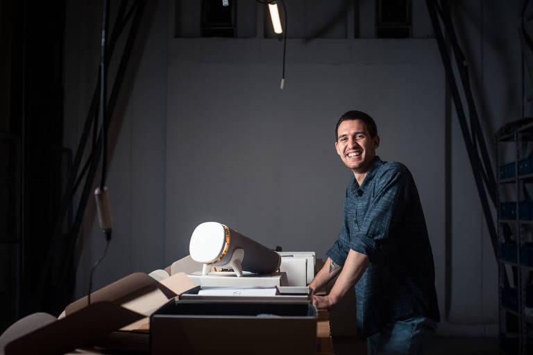 Rapaz sorri e está em pé, apoiado em uma mesa, com um luminária