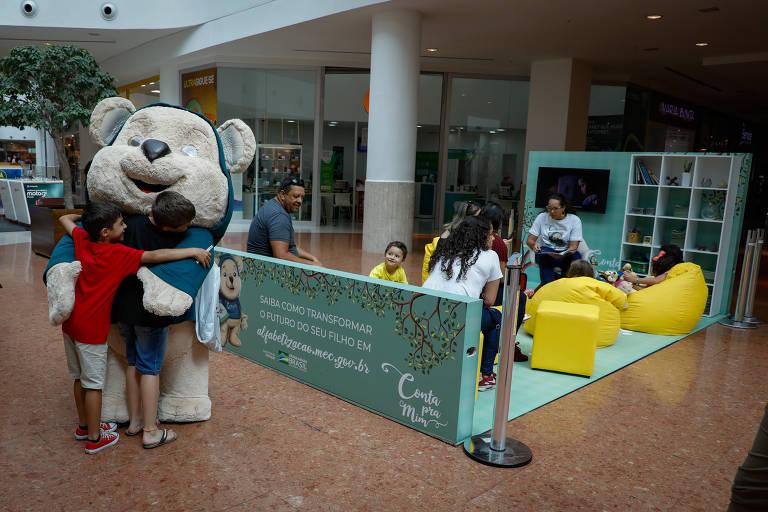 Ação da campanha Conta Pra Mim em shopping em Curitiba; urso Tito é abraçado por crianças em frente a estande de contação de histórias