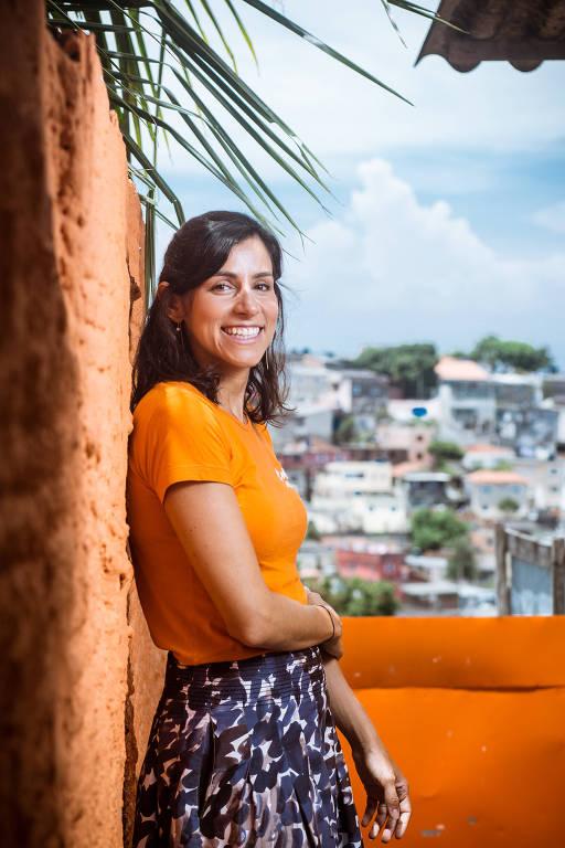Mulher jovem, vestida com saia e camiseta, sorri para foto. Há casas no fundo da imagem